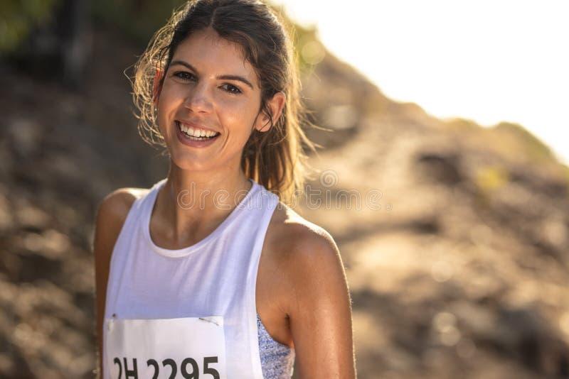 一个母赛跑者的画象在站立户外在山行迹的运动服的在种族期间 竞争在山的年轻女人 免版税库存照片
