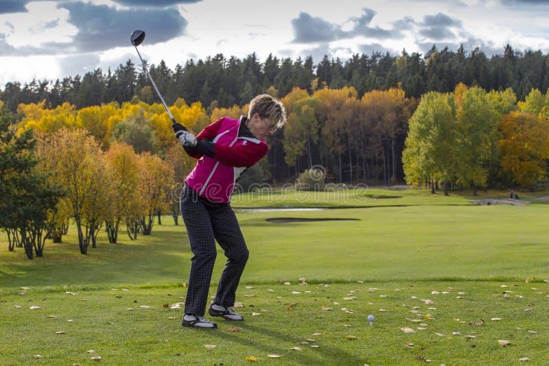 一个母高尔夫球运动员摇摆的司机,在一秋天天,在高尔夫球场 免版税库存照片