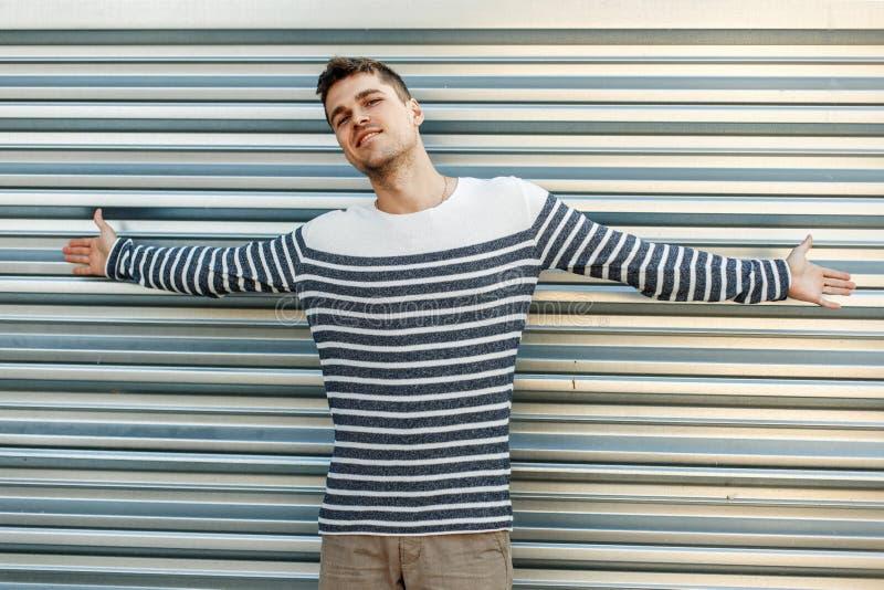 一个毛线衣无能为力的姿态的年轻人在金属墙壁附近 库存照片