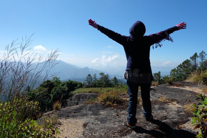 一个毛线衣身分的游人妇女在峭壁,用被举的手和看对天空和山 免版税库存照片