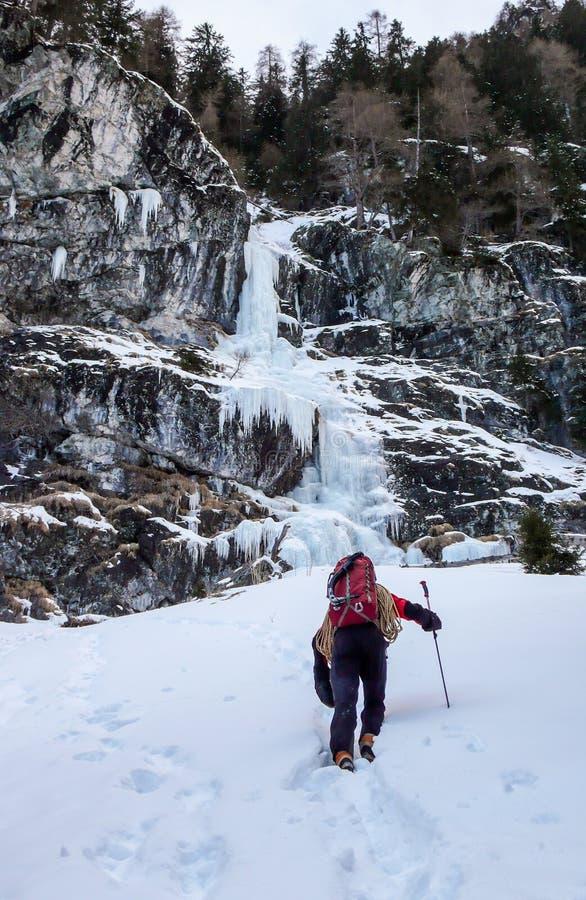 一个水兵和红色背包的男性冰登山人在一个美好的冬日接近冰崩并且准备攀登它 库存照片