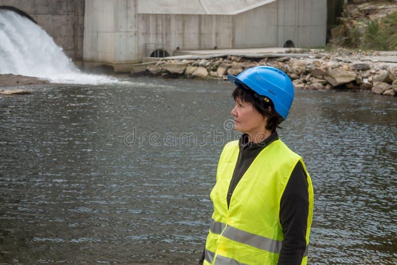 一个水力发电站的水坝和涡轮与下跌的水流量和女工的 免版税库存照片