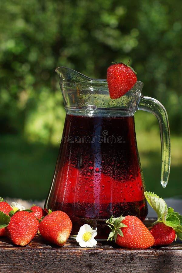 一个水罐用冷的草莓汁,盖用小滴,在与叶子的草莓旁边,采摘从庭院 库存图片