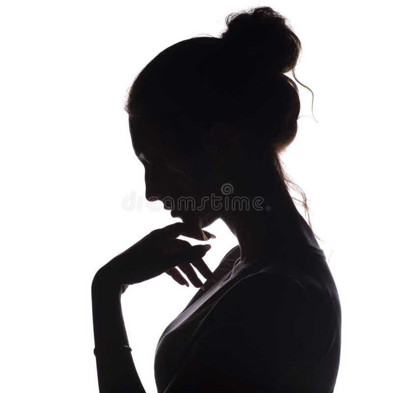 一个沉思女孩的外形剪影用在下巴的一只手,年轻女人降低了她的头下来在白色被隔绝的背景 免版税库存图片