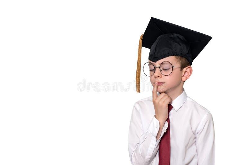 一个沉思男孩的画象白色衬衫、玻璃和一个学术盖帽的 E ?? 免版税库存照片