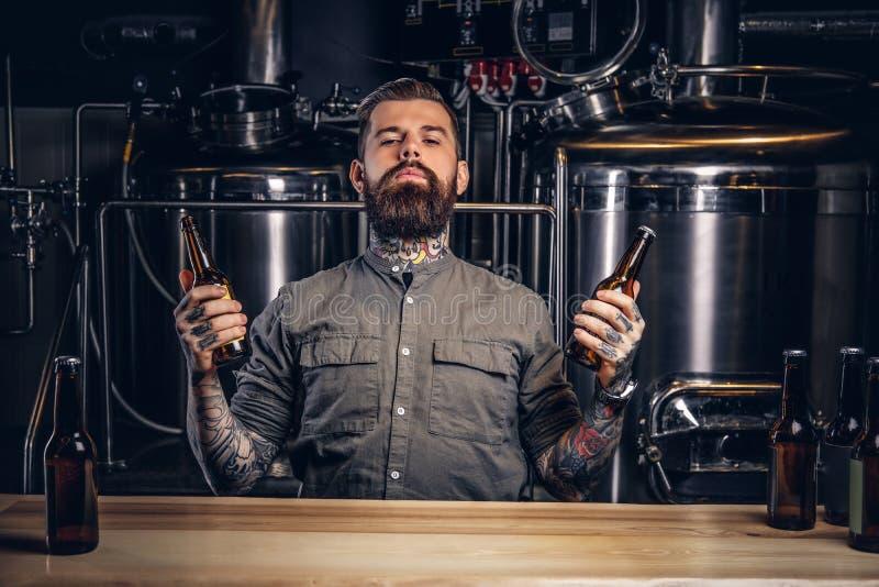 一个沉思被刺字的行家男性的画象与时髦的胡子的和头发拿着两个瓶用在制片人的工艺啤酒 免版税库存图片