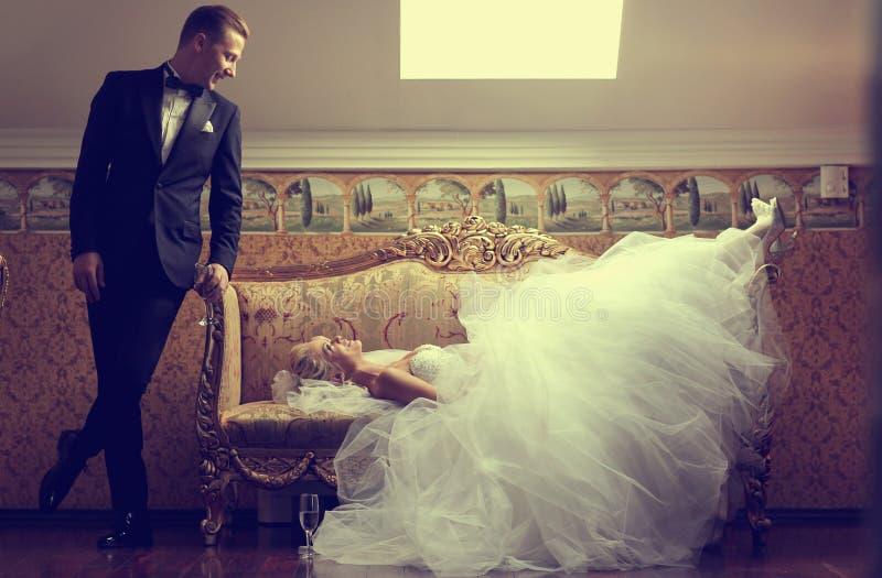 一个沙发和新郎的美丽的新娘在她附近在一家豪华旅馆里 库存图片