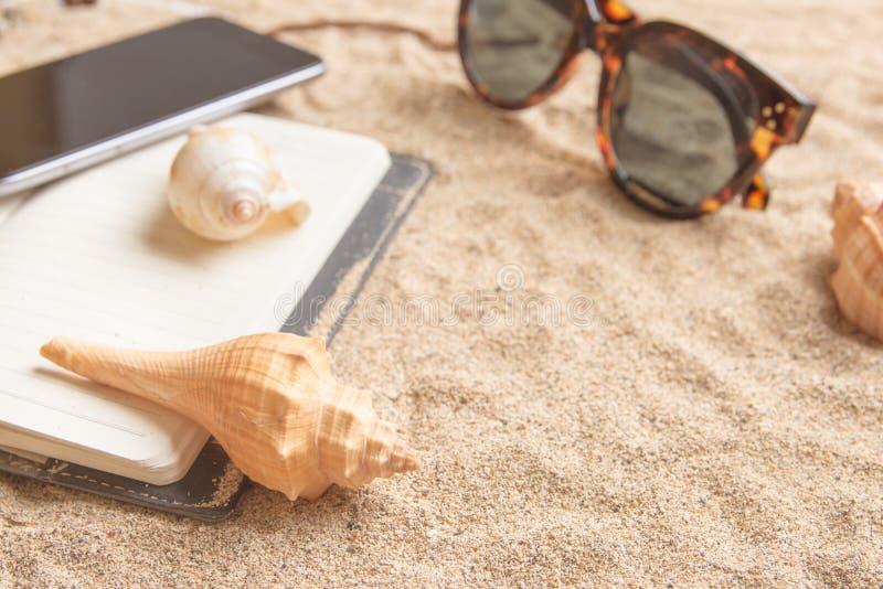 一个沙滩的每日计划者与壳、太阳镜和手机 库存照片