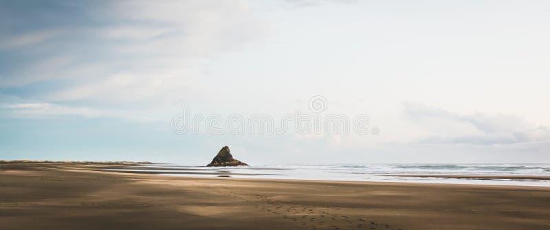 一个沙滩的美丽的全景射击与一个唯一岩石的在中间和惊人的天空 库存图片