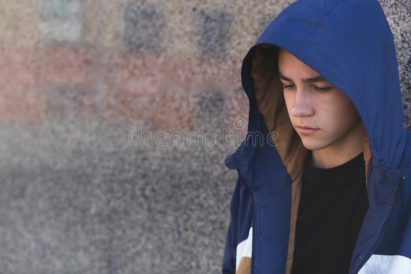 一个沮丧的哀伤的十几岁的男孩的画象黑暗的背景的,少年问题概念 库存图片