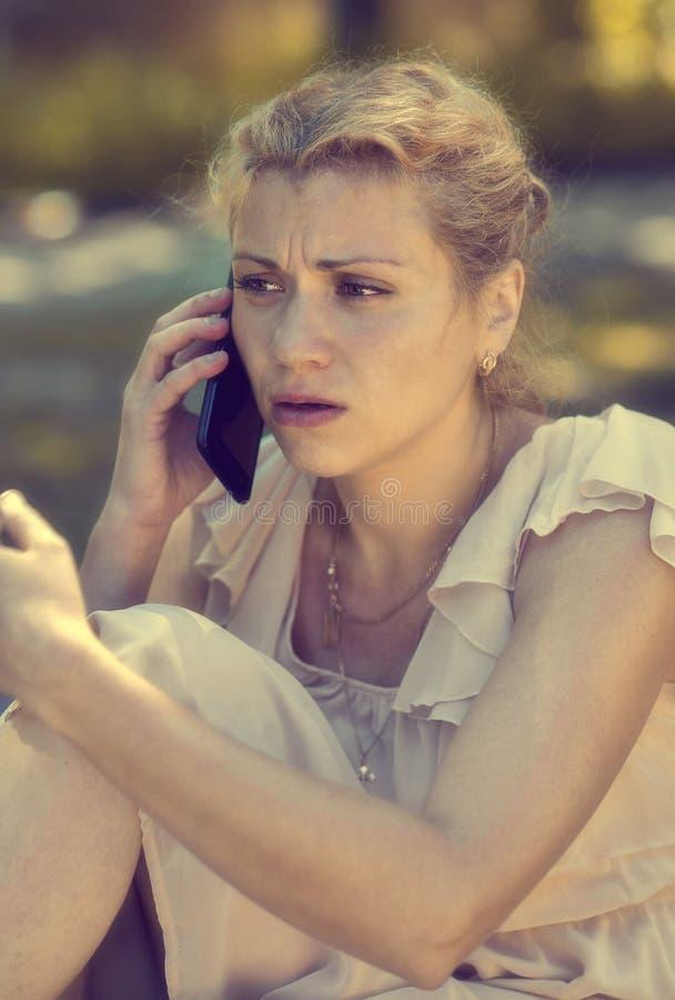 一个沮丧的女孩在电话里说 免版税库存照片