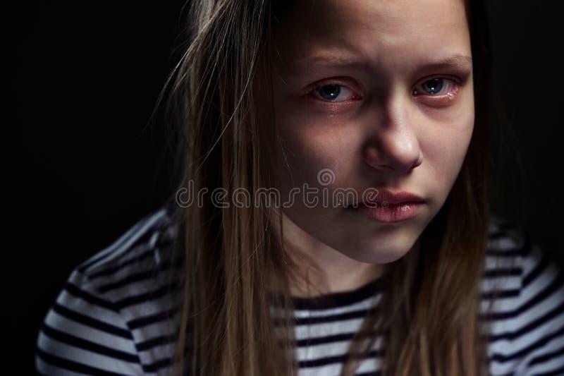 一个沮丧的青少年的女孩的黑暗的画象 免版税库存图片
