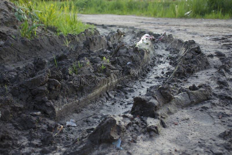一个泥泞的垄沟的特写镜头从车轮的 图库摄影