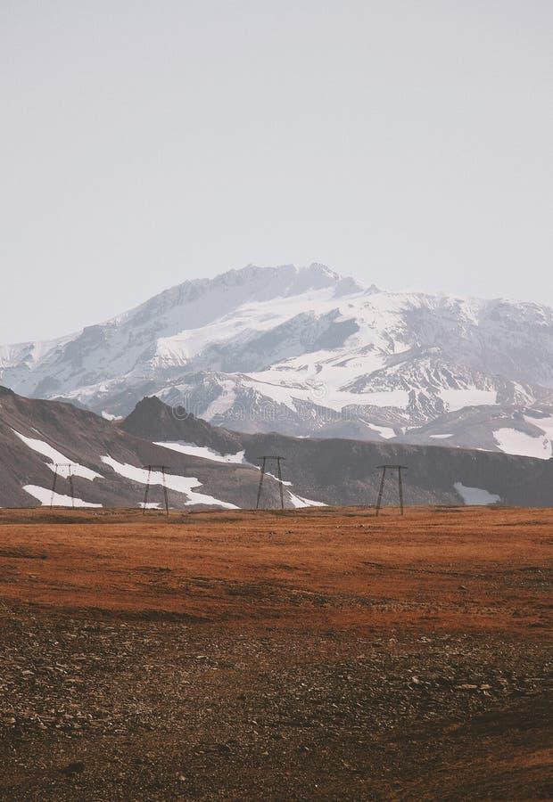 一个泥泞的领域的美丽的射击与使多雪的山惊奇的在背景中 图库摄影