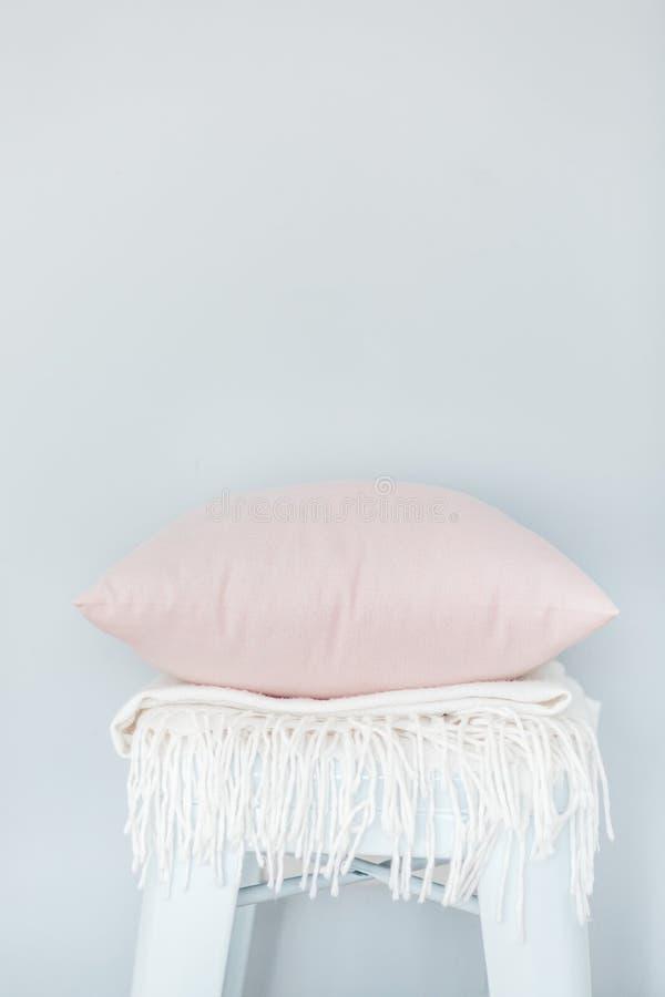 一个浅粉红色的枕头和白色格子花呢披肩的Minimalistic skandinavian图片在椅子在淡蓝的墙壁附近 免版税库存照片