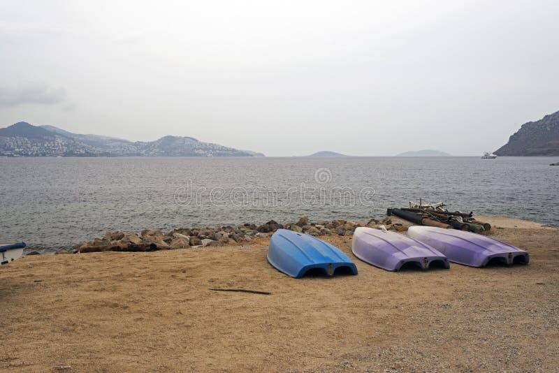 一个海滩和独木舟的看法在多云天气在博德鲁姆,土耳其 免版税库存照片