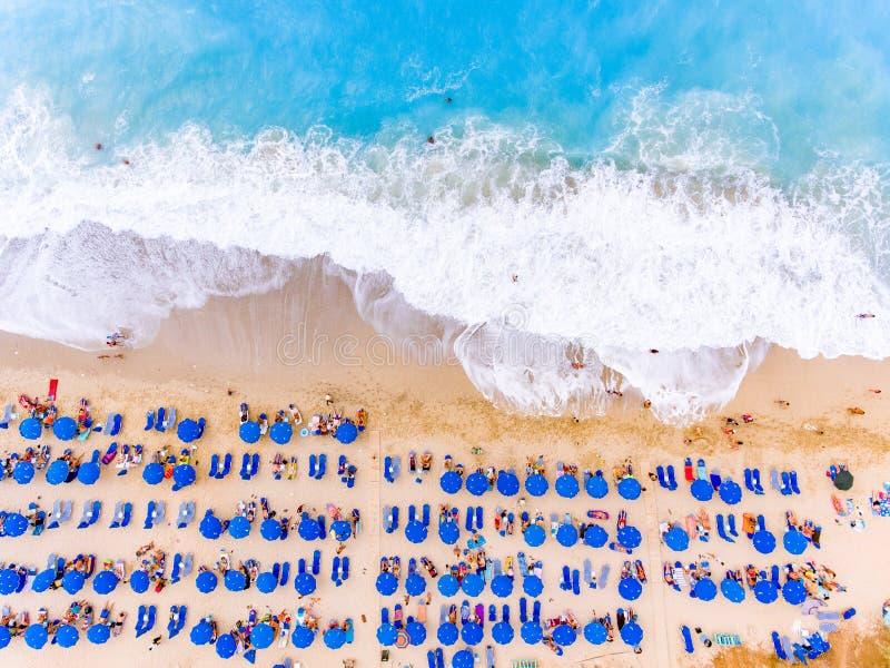 一个海滩的俯视图与大波浪、sunbeds和伞的 库存图片