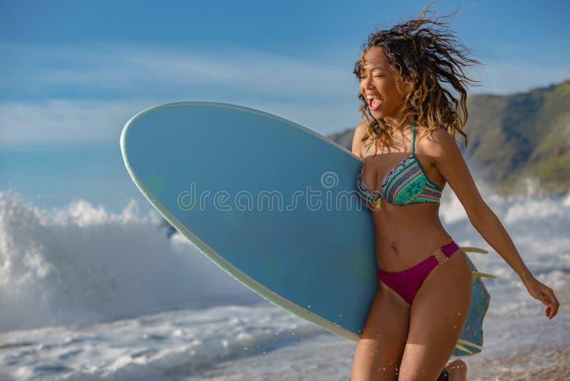 一个海滩的微笑的愉快的女孩与冲浪板 免版税图库摄影