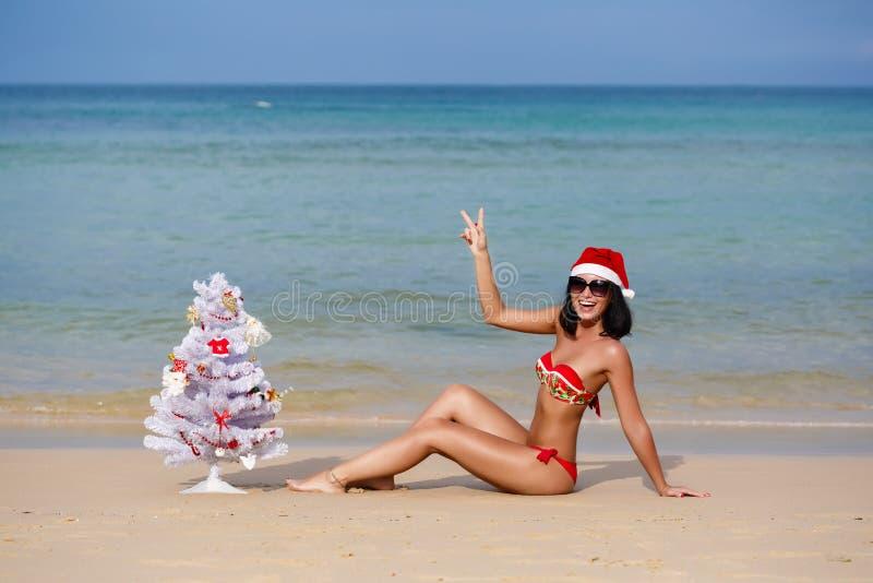 一个海滩的性感的女孩在圣诞老人的礼服 库存照片