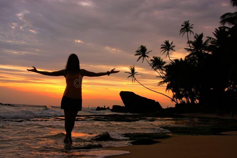 一个海滩的现出轮廓的妇女与棕榈树和岩石在日落 图库摄影
