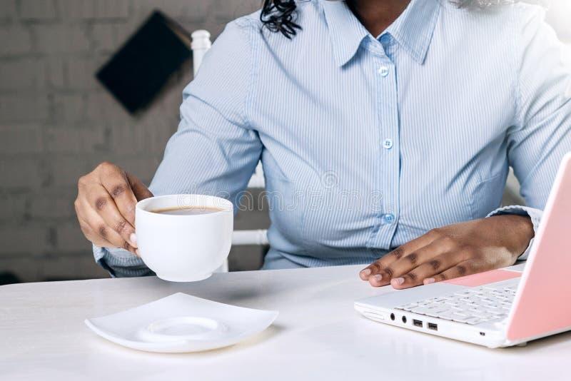 一个深色皮肤的女孩的手有一个杯子的在桌的芳香早晨咖啡 免版税库存照片