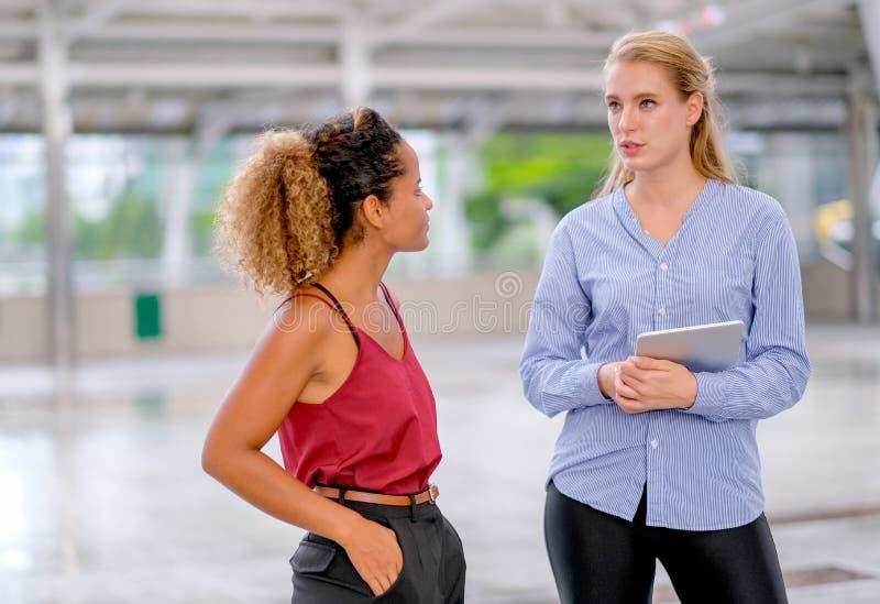 一个混合的族种女孩立场和与拿着片剂的白白种人女孩谈论 免版税图库摄影