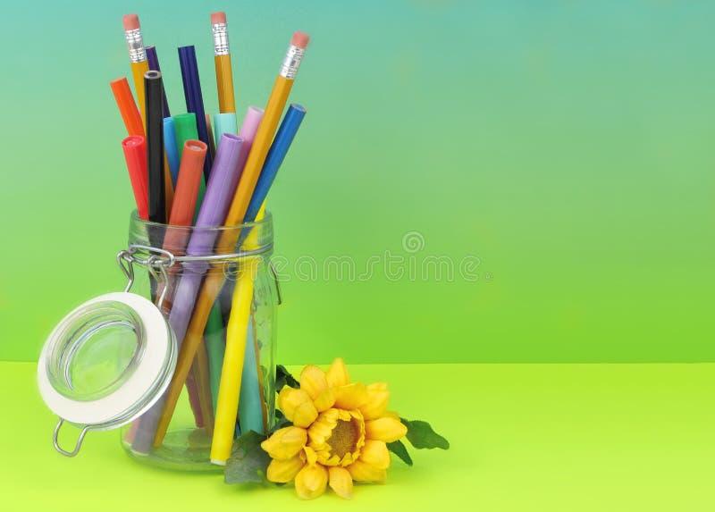 一个清楚的密封瓶子充满五颜六色的制造商和铅笔在一毕业的蓝绿色blackground与黄色丝绸花 免版税图库摄影