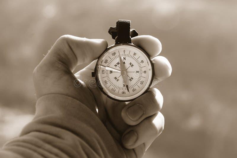 一个游人的特写镜头手有一个地道指南针的在一个山路风景的背景在温暖乌贼属定调子的 免版税图库摄影