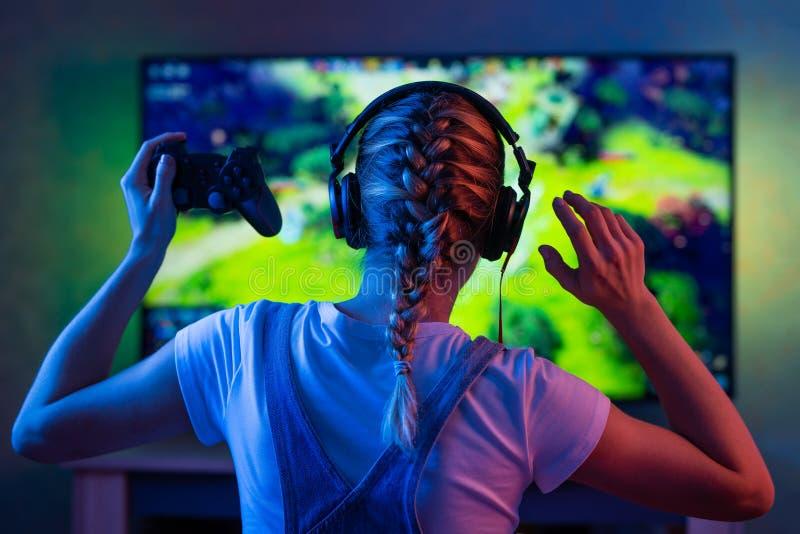 一个游戏玩家或一个飘带女孩在家在有使用与网络的朋友的gamepad的一个暗室在电子游戏 一个年轻人 免版税图库摄影