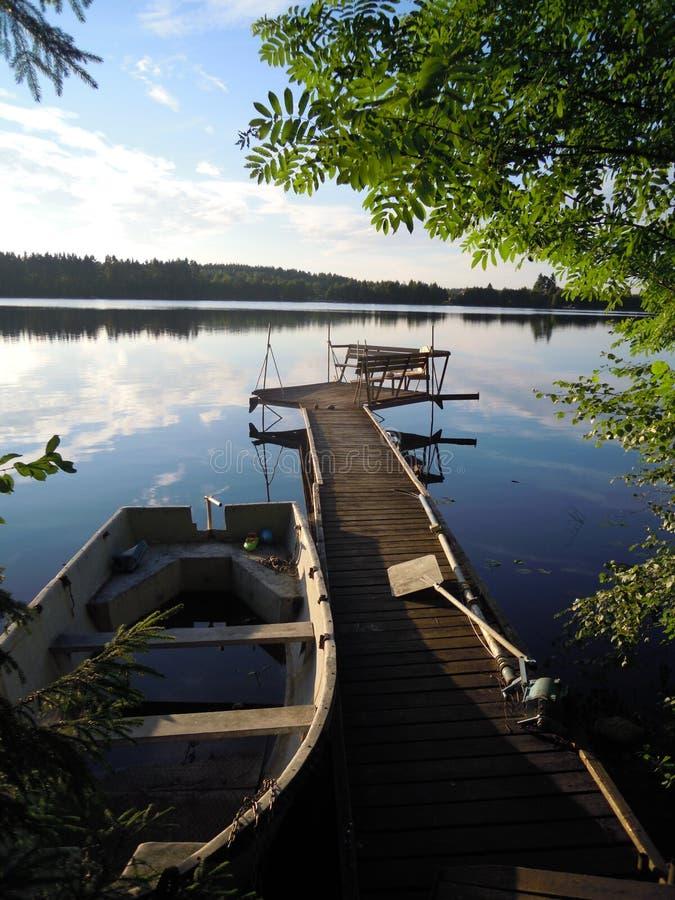 一个湖、一条老小船和木走道在一个晴朗的夏日 免版税库存照片