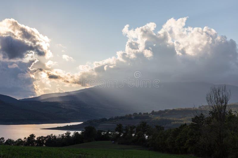 一个湖和小山的美丽的景色,与太阳发出光线过滤的thro 免版税图库摄影