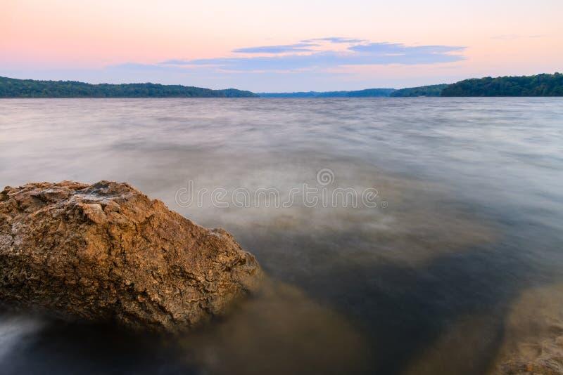一个湖的岩石海岸线日落的 免版税图库摄影