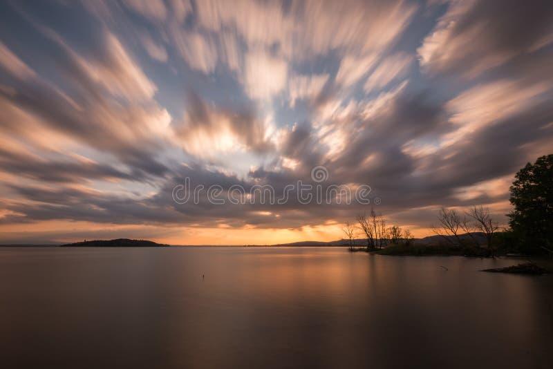 一个湖的美好的广角,长的曝光视图日落的,与与移动的云彩的巨大的天空 免版税库存图片