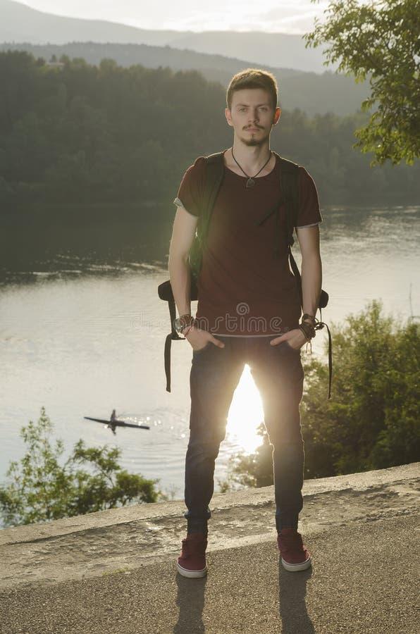 一个湖的年轻人有背包的 免版税库存照片