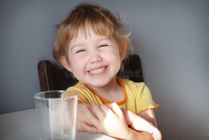 一个滑稽的孩子的画象灰色背景的在桌特写镜头 滑稽的滑稽动作 免版税库存图片