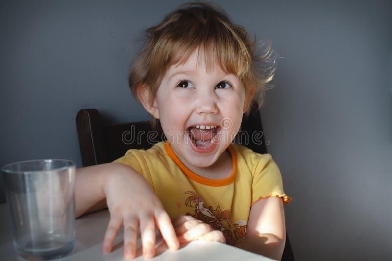 一个滑稽的孩子的画象灰色背景的在桌特写镜头 滑稽的滑稽动作 恶作剧孩子 免版税库存图片