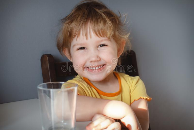 一个滑稽的孩子的画象灰色背景的在桌特写镜头 滑稽的滑稽动作 图库摄影