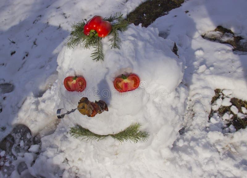 一个滑稽的雪人由雪制成 与烤肉的雪人在他的鼻子 库存图片