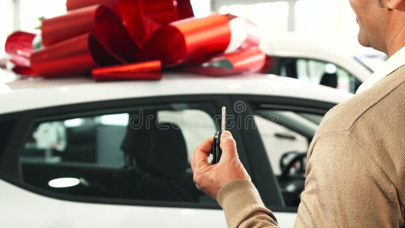 一个满意的人看他新的汽车并且显示钥匙对它 免版税库存图片