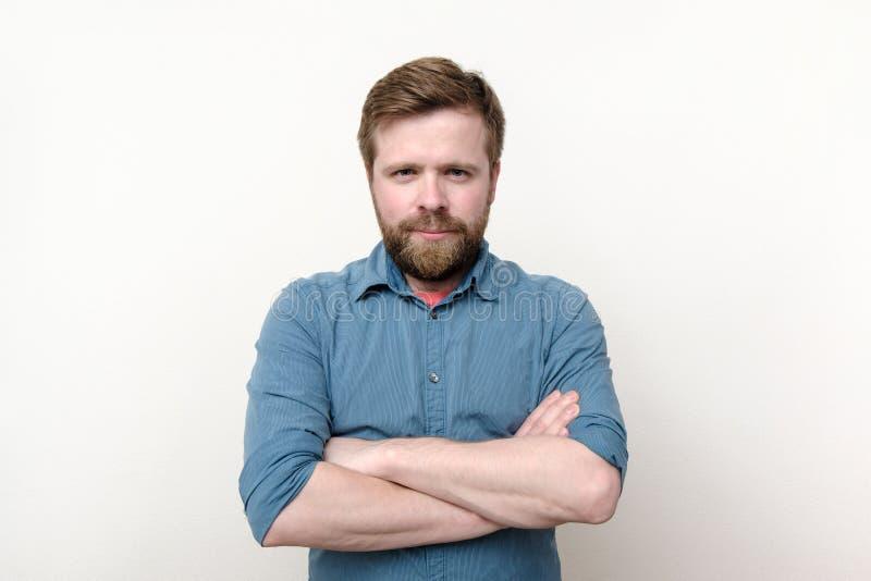 一个满足的有胡子的人确信地站立与他的双臂专心地被交叉的和凝视 r 库存图片