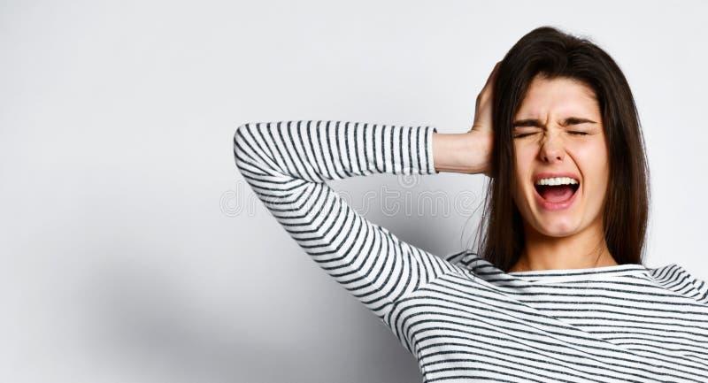 一个激动的叫喊的年轻女人身分的图象在轻的背景的 免版税库存图片