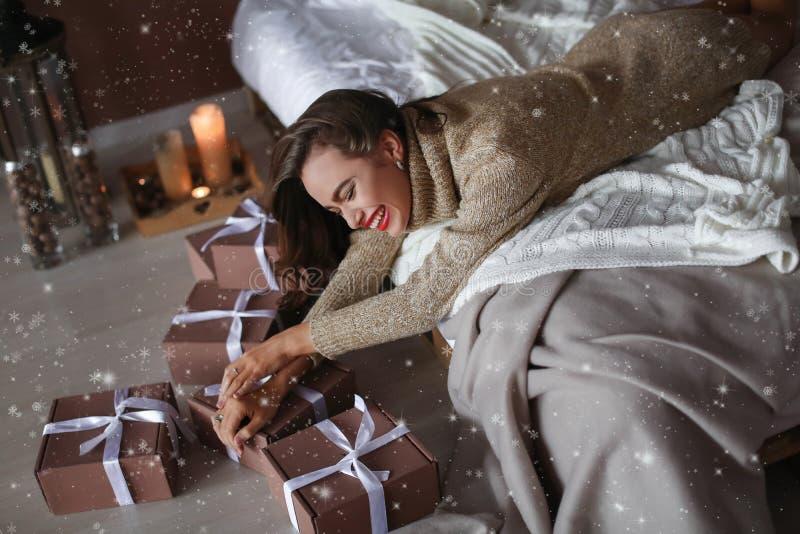 一个激动的年轻女人打开的当前箱子的接近的画象,当在家时在床上 免版税库存照片