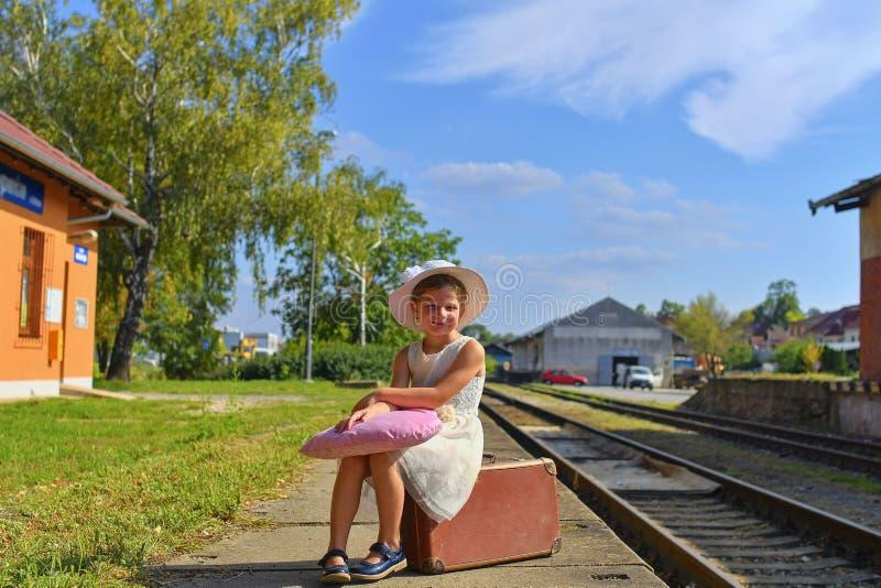 一个火车站的可爱的小女孩,等待带着葡萄酒手提箱的火车 旅行,假日和chilhood 免版税库存图片