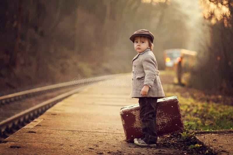 一个火车站的可爱的男孩,等待有手提箱和玩具熊的火车 免版税库存图片
