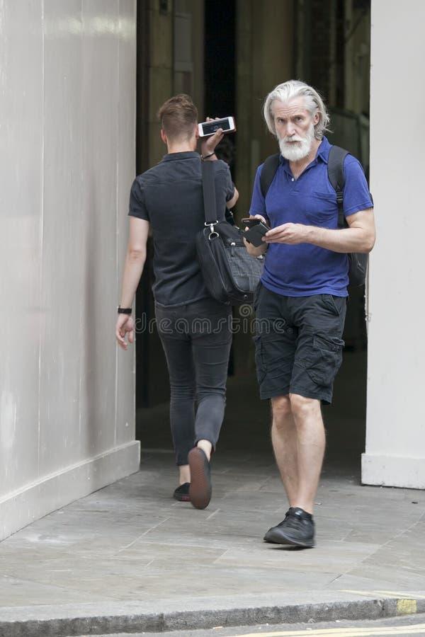 一个灰发的中年人简而言之站立在街道上的 免版税库存图片