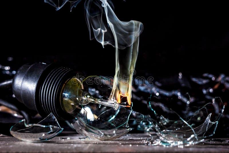 一个灼烧的电灯泡的令人惊讶的爆炸与裂片和烟的 免版税库存图片