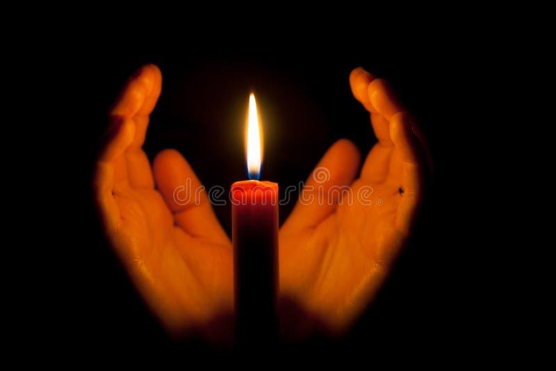 一个灼烧的蜡烛在晚上,围拢由妇女的手 生活的标志、爱和光、保护和温暖 库存照片