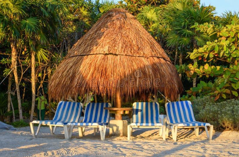 一个热带沙滩的看法与秸杆伞和躺椅的 免版税库存照片