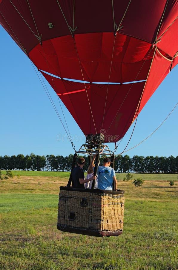 一个热空气气球的长平底船有三名浮升员的从地面离开并且开始上升 免版税库存照片