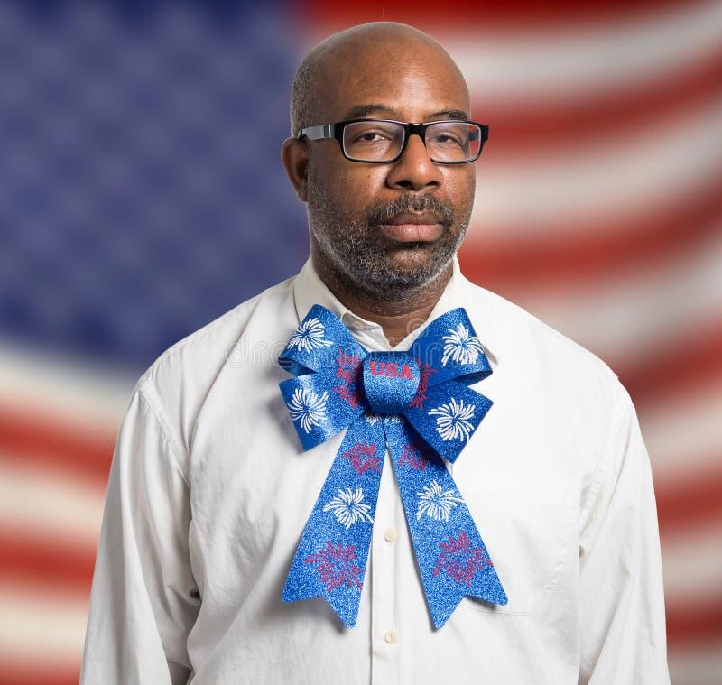 一个爱国的非裔美国人的人的画象有玻璃和美国独立纪念日蝶形领结的反对美国国旗背景 免版税库存照片